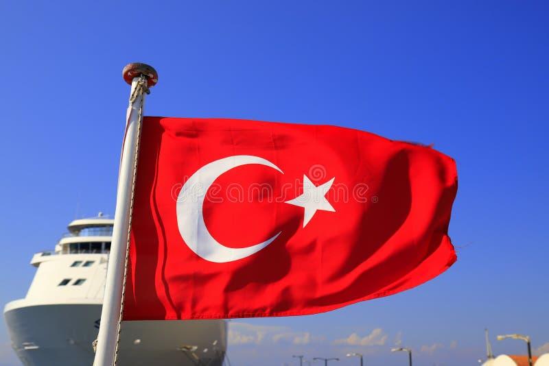 Красный национальный флаг Турции с половинным месяцем и звезда против голубого неба и большого белого океанского лайнера, турецко стоковые фото