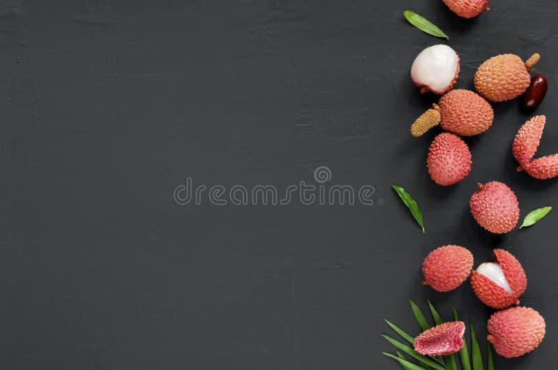Красный органический плод lychee на черной каменной деревенской предпосылке, взгляде сверху стоковое фото rf