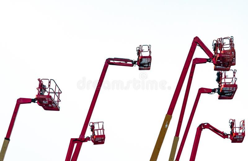 Красный отчетливо произношенный подъем заграждения Воздушный подъем платформы Телескопичный подъем заграждения изолированный на б стоковые фотографии rf