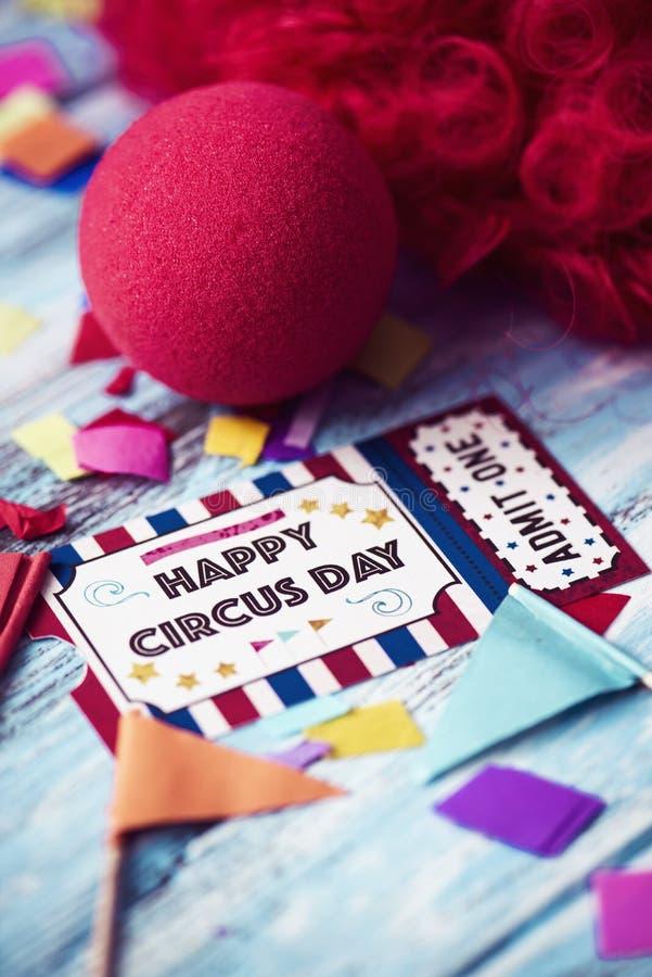 Красный парик, нос клоуна и день цирка текста счастливый стоковое фото rf