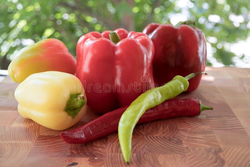 Красный перец салата и зеленый горячий перец на деревянной доске на солнечный день на зеленой предпосылке стоковые изображения rf
