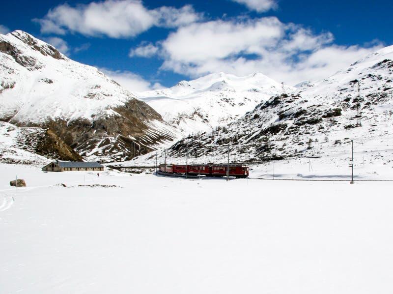 Красный поезд в ландшафте зимы около St Moritz в швейцарских Альпах стоковые изображения