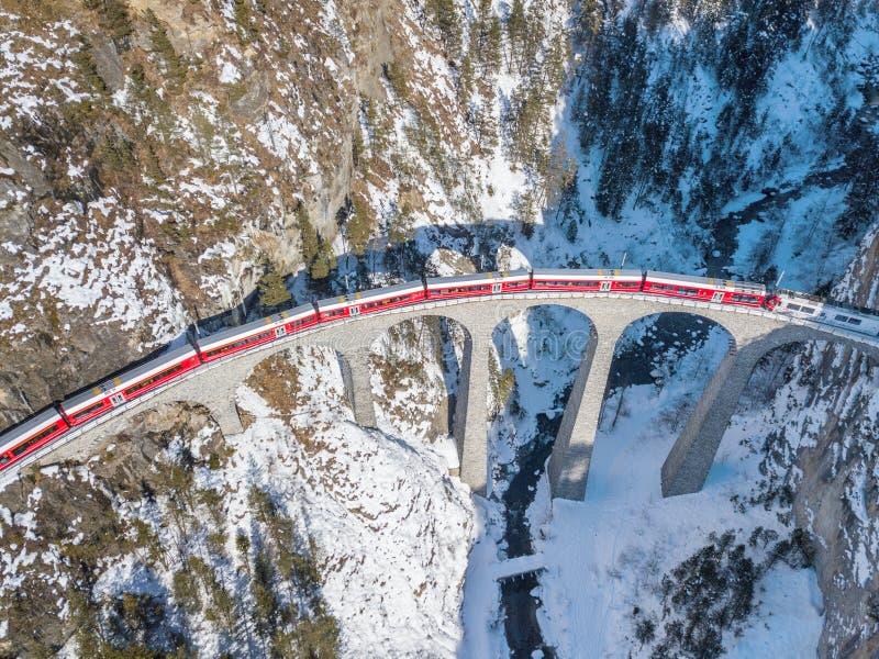 Красный поезд проходя на известный виадук Landwasser стоковые изображения rf