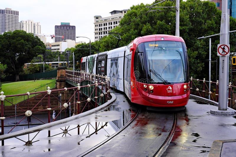 Красный поезд рельса света Сиднея причаливая центральному железнодорожному вокзалу, Австралии стоковые изображения rf