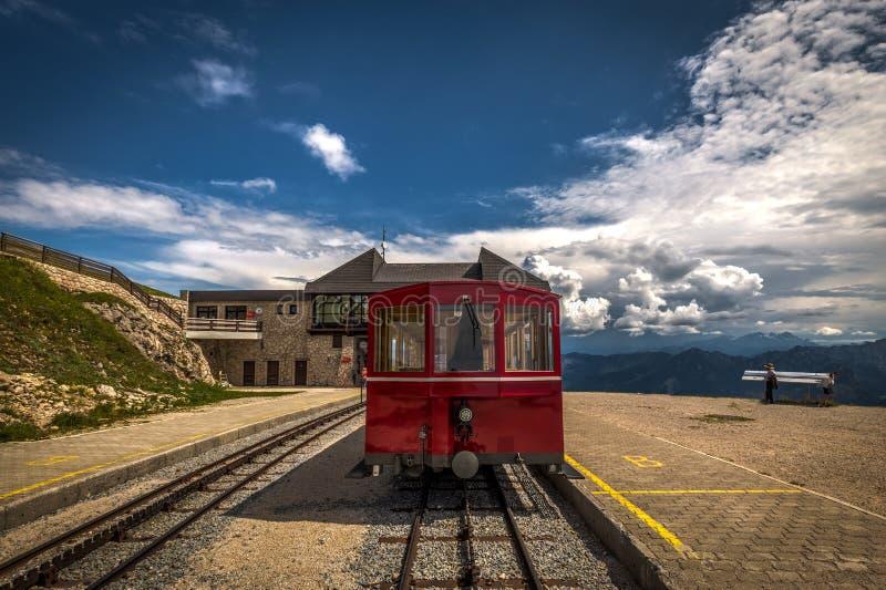 Красный поезд cogwheel шкафа пара ждать в станции Schafbergspitze на пике горного пика Schafberg в австрийце стоковые изображения