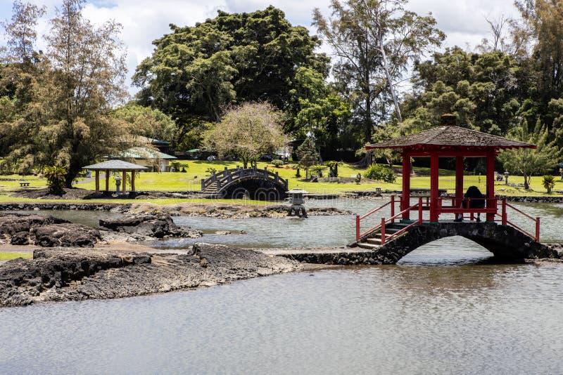 Красный покрытый footbridge с каменными мостом и парком стоковые фото