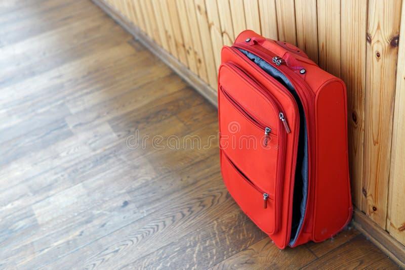 Красный полу-открытый новый чемодан на деревянной предпосылке стоковые фотографии rf