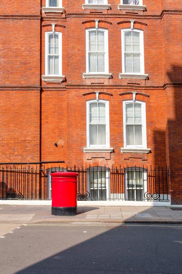 Красный почтовый ящик в улицах Лондона стоковые фото
