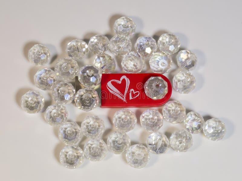 Красный привод вспышки USB с сердцем, самоцветами на светлой предпосылке стоковая фотография rf