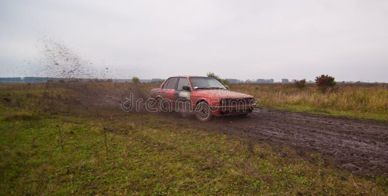Красный привод спортивной машины на грязи стоковая фотография