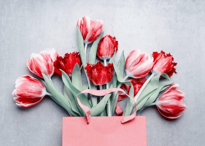 Красный пук тюльпанов в бумажной хозяйственной сумке на серой предпосылке Праздничные цветки весны Флористический составлять Праз стоковая фотография rf