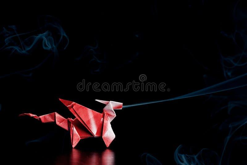 Красный дракон Origami с голубым дымом стоковое фото rf