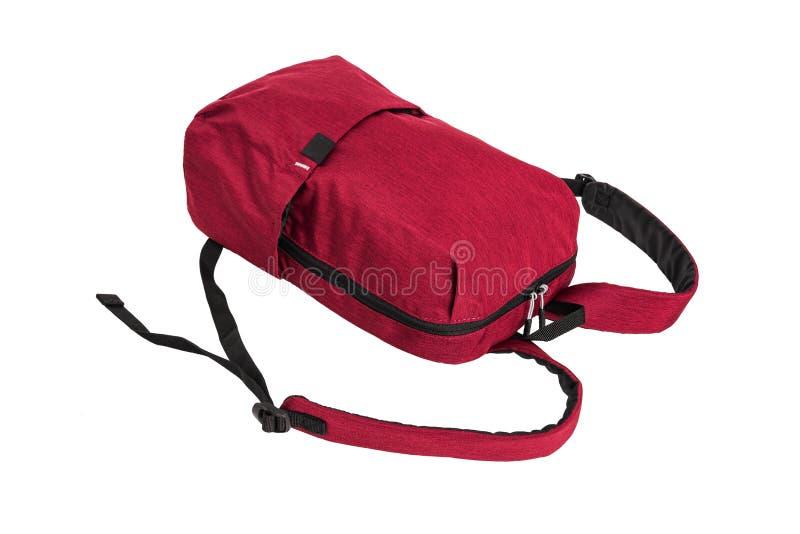 Красный рюкзак лежит, изоляция на белой предпосылке стоковое изображение