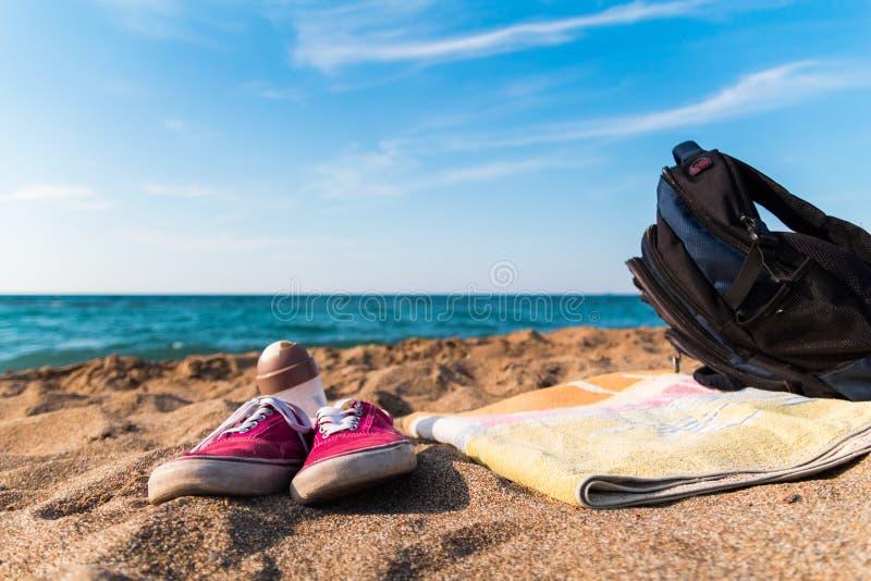 Красный рюкзак полотенца ботинок на море песчаного пляжа как предпосылка быстрое пикирование избежание пляжа свобода лета стоковое фото rf