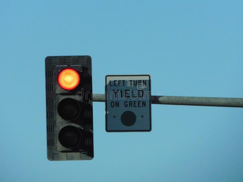 Красный светофор с выходом на зеленом знаке стоковое фото