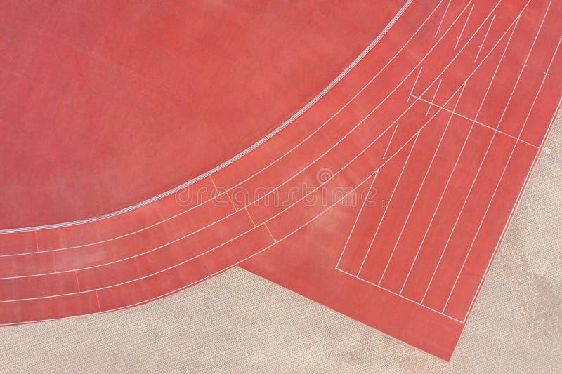 Красный синтетический резиновый атлетический идущий след на стадионе r стоковая фотография rf