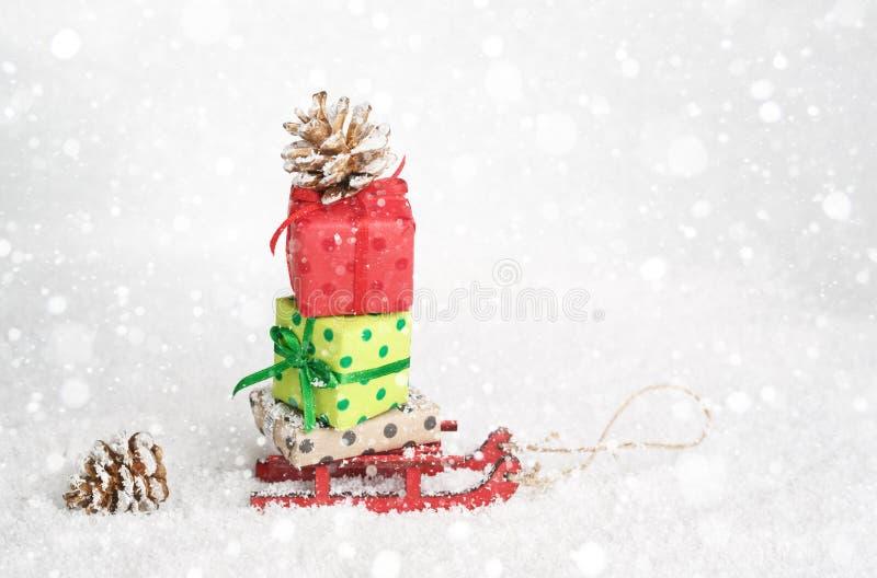 Красный скелетон поставляя подарки рождества или Нового Года на снежном сияющем f стоковые фотографии rf