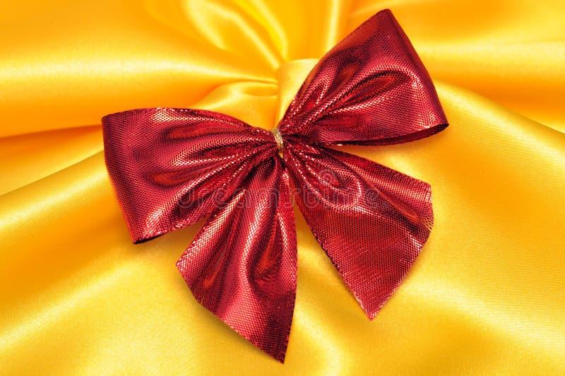 Красный смычок на желтой сатинировке стоковое фото rf