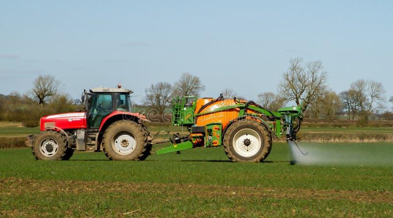 Красный современный трактор вытягивая спрейер урожая стоковые изображения
