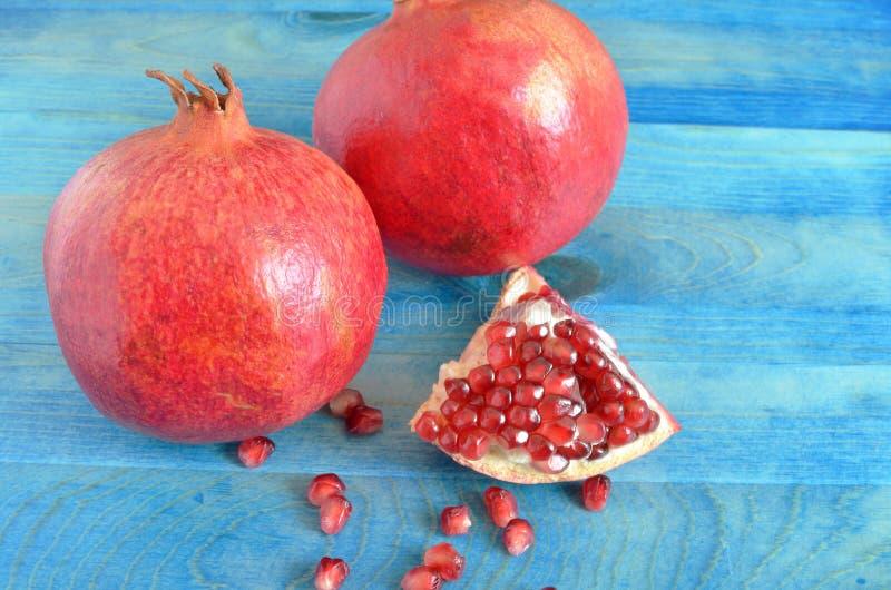 Красный сочный плодоовощ гранатового дерева с красными семенами на голубой деревянной предпосылке стоковое фото