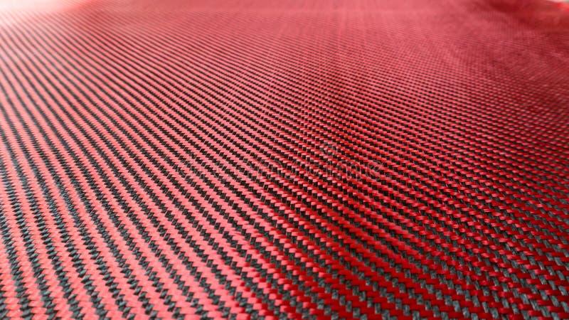 Красный сплетенный черный конец предпосылки композиционного материала волокна углерода вверх по взгляду стоковые изображения