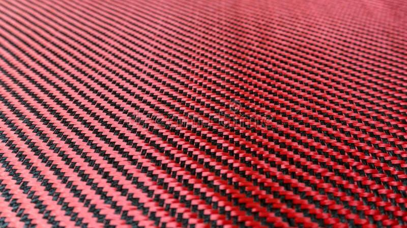 Красный сплетенный черный конец предпосылки композиционного материала волокна углерода вверх по взгляду стоковые фотографии rf