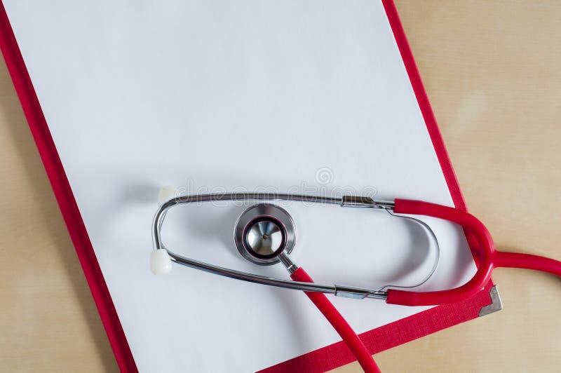 Красный стетоскоп на красной доске сзажимом для бумаги Медицинская служба Обработка, здравоохранение Рассмотрение сердца Изучать  стоковые фотографии rf