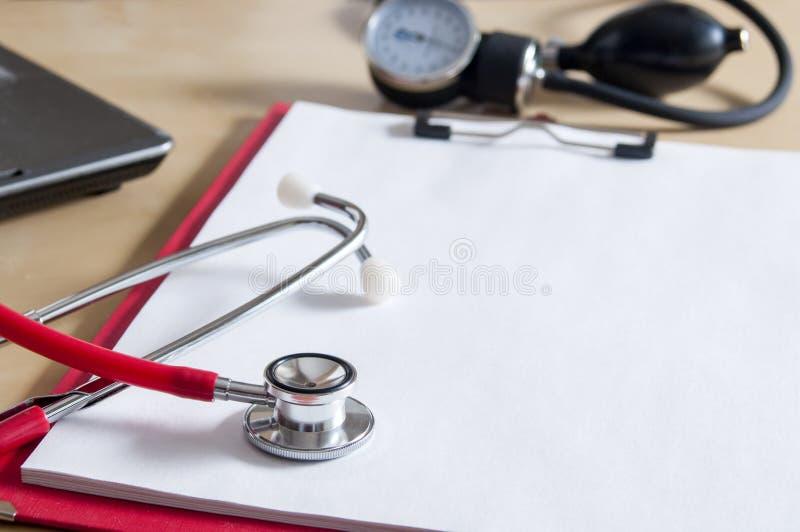 Красный стетоскоп на красной доске сзажимом для бумаги Около ноутбука и tonometer r E Обработка, здравоохранение E стоковые изображения rf