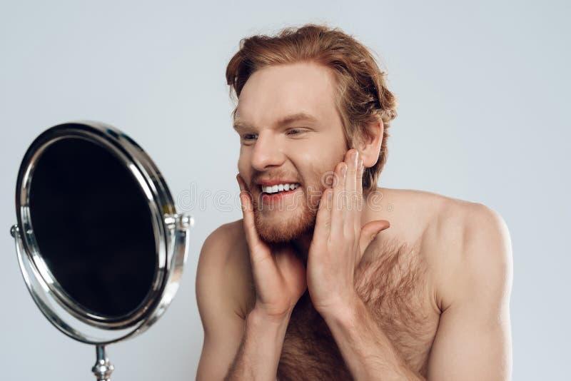 Красный с волосами молодой человек штрихуя бороду стоковые фотографии rf