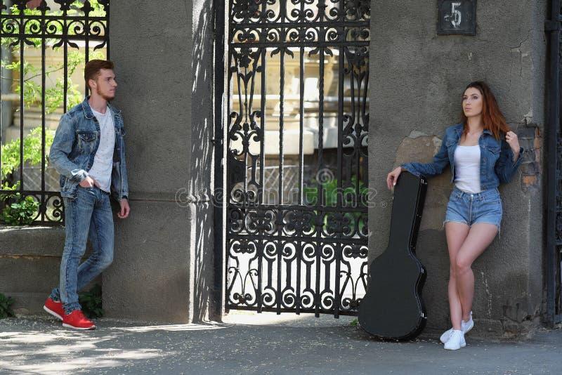 Красный с волосами парень и красная с волосами девушка имея потеху играя гитару стоковые фото