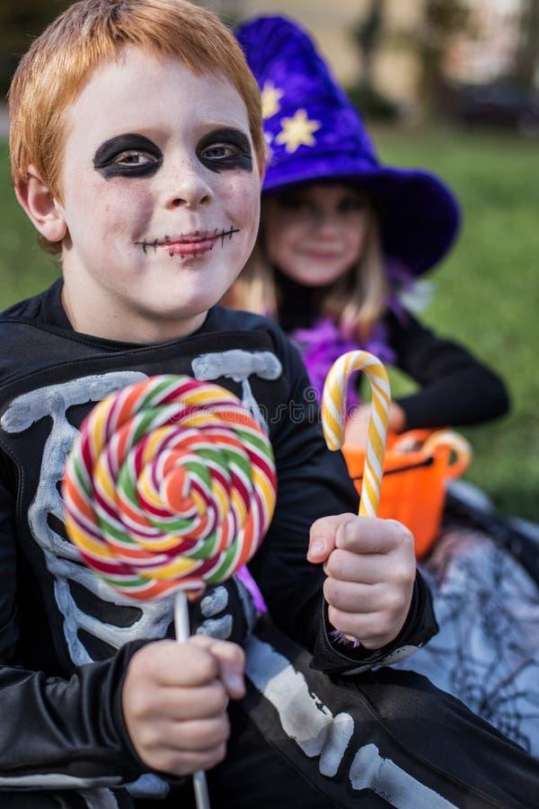 Красный с волосами мальчик нося костюм хеллоуина каркасный и держа красочные конфеты стоковое изображение rf