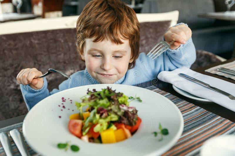 Красный с волосами мальчик с вилками есть салат стоковые фото