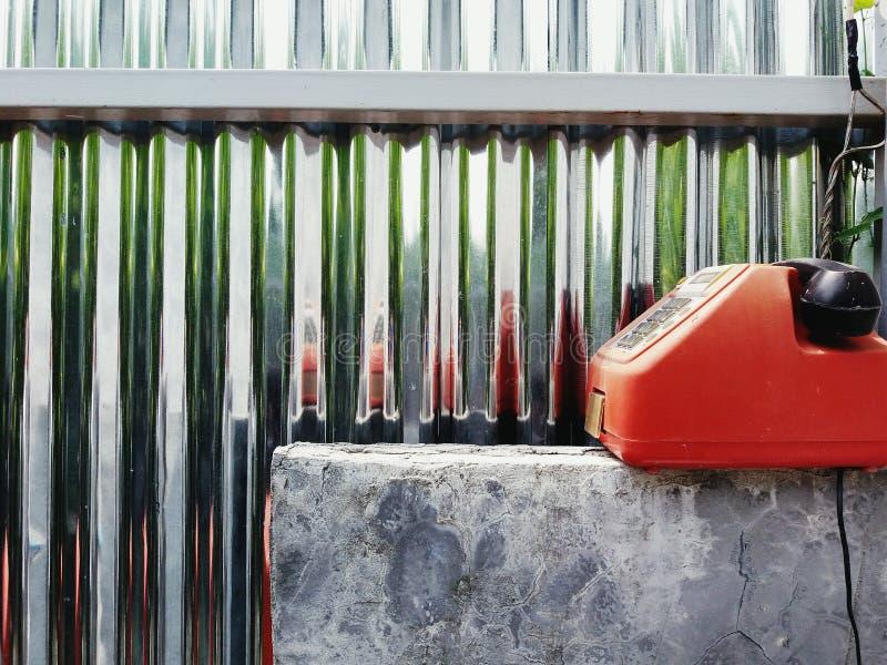 Красный телефон года сбора винограда, ретро или старых при черная телефонная трубка кладя на конкретную таблицу стоковое изображение