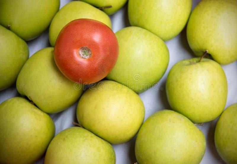 Красный томат на зеленых яблоках стоковое фото