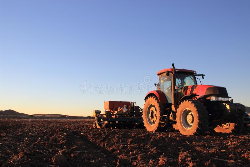 Красный трактор в открытом поле с плантатором стоковая фотография rf