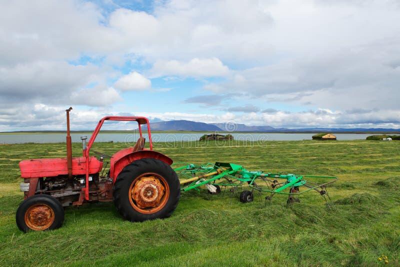 Красный трактор в поле перед озером, Исландией стоковые фотографии rf