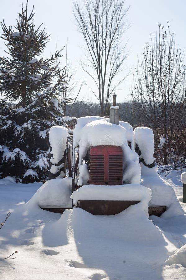 Красный трактор в снеге стоковое фото rf