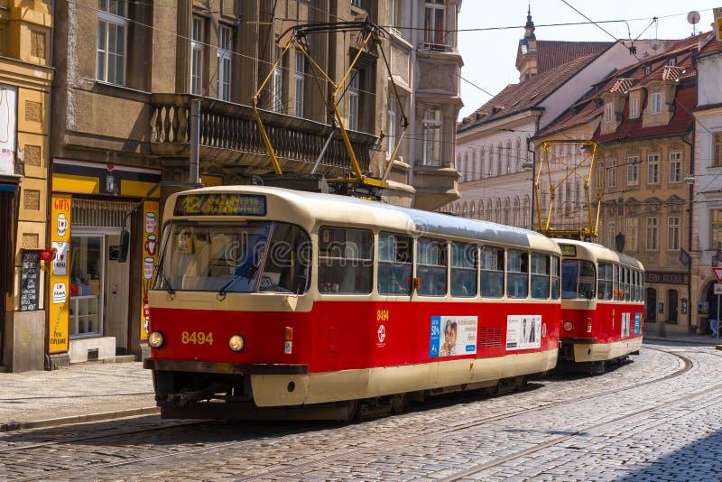 Красный трамвай на улице булыжника в Праге стоковое фото rf