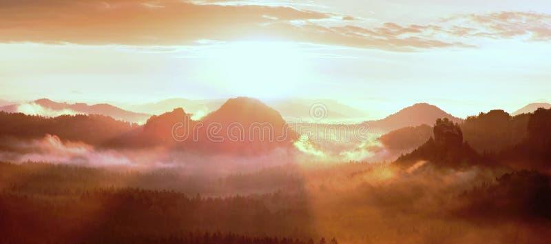 Красный туманный рассвет в красивые холмы Пики холмов вставляют вне от туманного тумана предпосылки, красного цвета и апельсина п стоковое фото