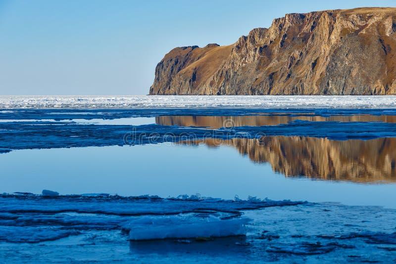 Красный утес на озере Байкал с плавя льдом стоковые фотографии rf