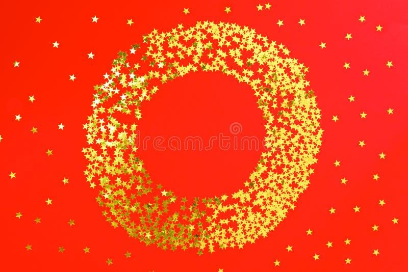 Красный фон с ярким блеском и золотой confetti звезд в круге Предпосылка праздничного праздника яркая стоковые изображения rf