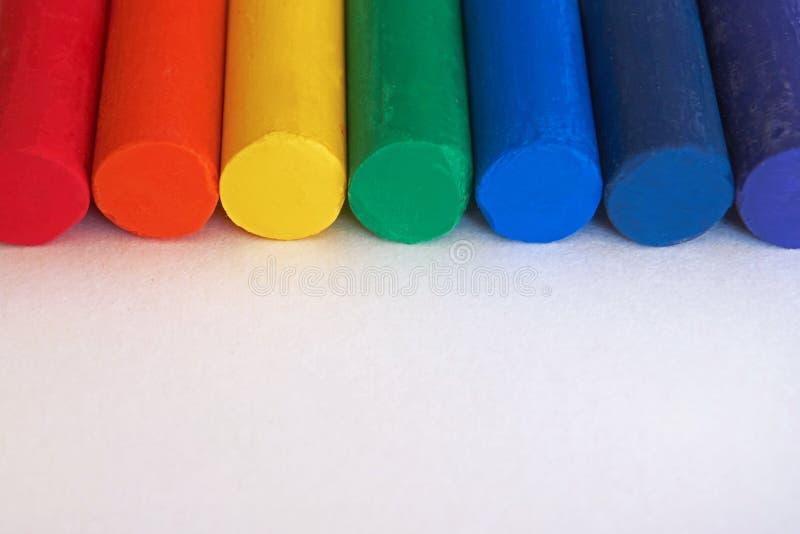 Красный цвет, апельсин, желтый цвет, зеленый цвет, синь, индиго, фиолетовое Crayons покрашенные радугой помещенная сторона - мимо стоковые изображения rf