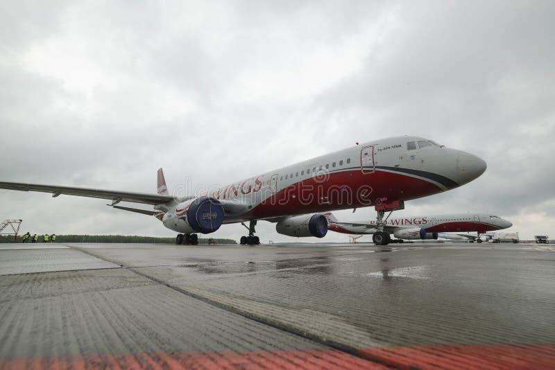 Красный цвет воздушных судн Tupolev-204 подгоняет авиакомпанию в месте для стоянки стоковые фотографии rf