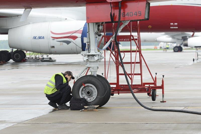Красный цвет воздушных судн Tupolev-204 подгоняет авиакомпанию в месте для стоянки стоковая фотография