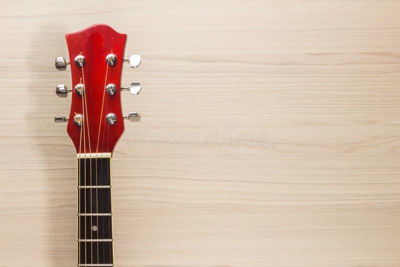 Красный цвет гитары акустический, шея лежит на испанской деревянной предпосылки света стены классической, прямоугольной музыке фо стоковое фото rf