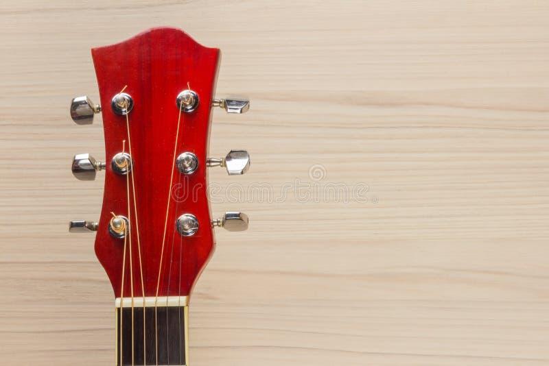 Красный цвет гитары акустический, шея лежит на испанской деревянной предпосылки света стены классической, прямоугольной музыке фо стоковое фото