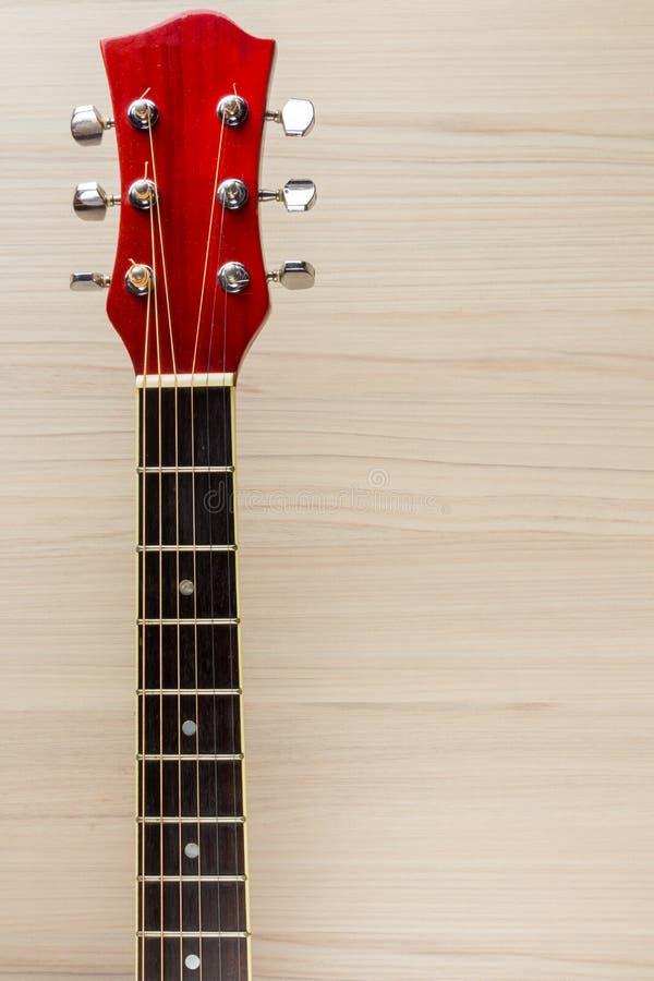 Красный цвет гитары акустический, шея отдыхает на испанской деревянной светлой предпосылки классической, музыкальной игре школы д стоковое фото rf