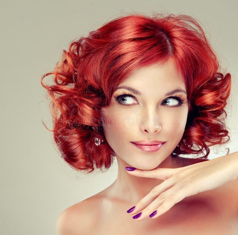 красный цвет девушки с волосами довольно стоковые фото