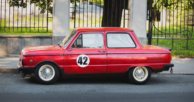 Красный цвет настроил ретро автомобиль припаркованный на дороге стоковые фото