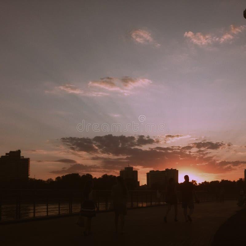 Красный цвет неба людей лета улицы солнца вечера города идя стоковые изображения rf